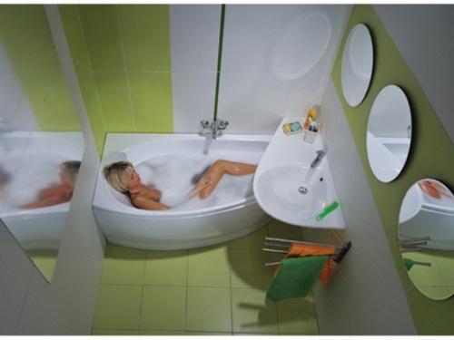 Интерьер маленькой ванной комнаты с угловой ванной