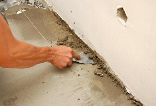 Срезаем наплывы стяжки возле стен