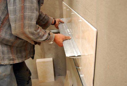 Проверяем ровно ли уложена плитка алюминиевой рейкой