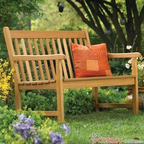 Садовая скамейка на газоне фото